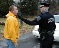 police officer administers a breathalyzer test